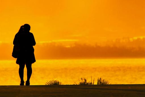 Silhouette of a high school girl with a ponytail dyed in the setting sun