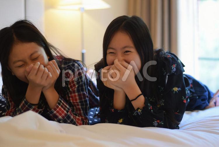 口を押さえて大笑いする姉妹の写真