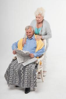 Foreigner senior couple sitting in chair and reading newspaper 3