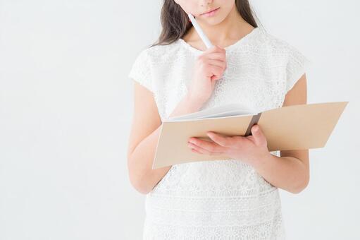 Girl thinking looking at notebook