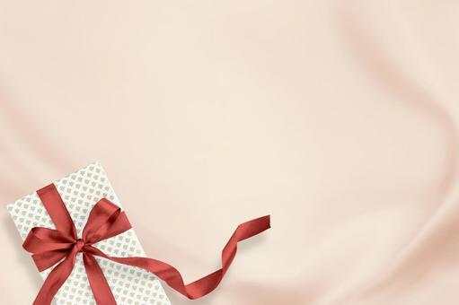 핑크 실크 배경에 빨간 리본 선물 상자