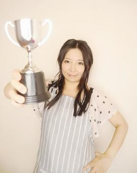 Woman in apron with championship trophy