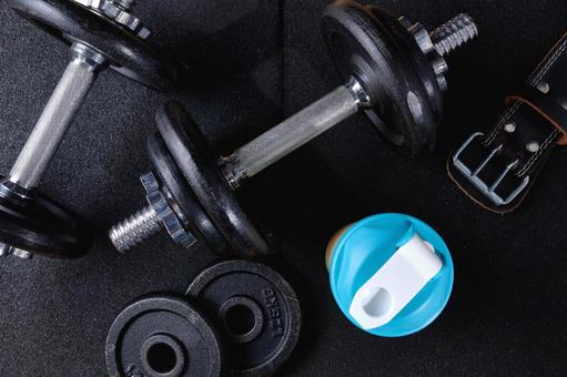 Protein and dumbbells on a rubber mat