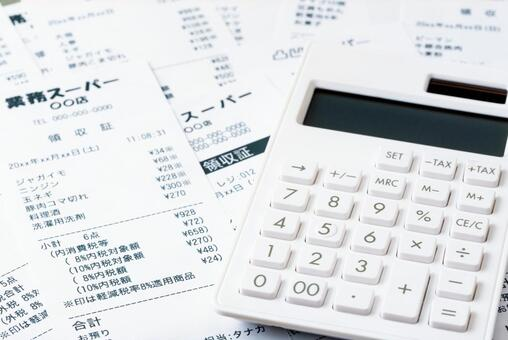Calculator and a large number of supermarket receipts (image of household budget management and savings)
