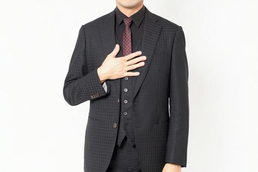 A male businessman standing in front of a white background and putting his hand on his chest