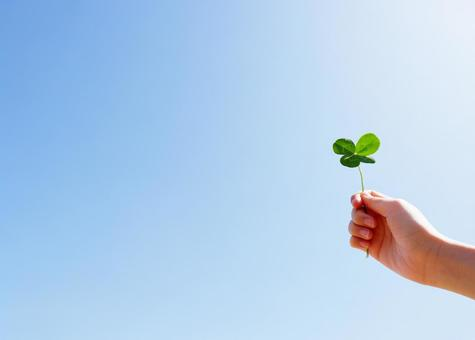 Hand with four-leaf clover and blue sky 01 Image of happiness Background material