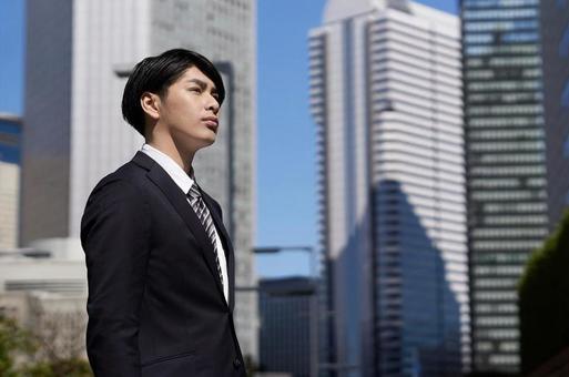 오피스 거리에서 진지한 표정으로 서 일본인 남성 사업가