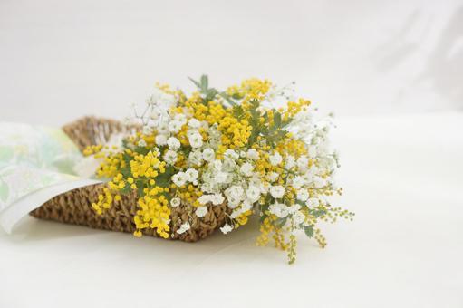 바구니에 놓인 미모사와 안개꽃의 꽃다발