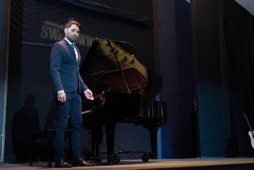 A man with a suit standing beside the piano 4