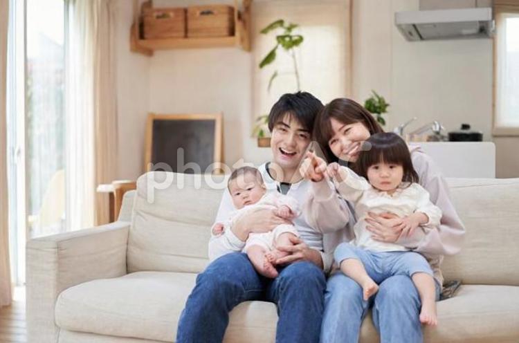 全員でテレビを見るアジア人ファミリーの写真