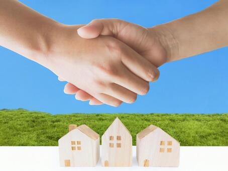Hand shaking hands of man and woman with blue sky and meadow and house-Newlywed life image