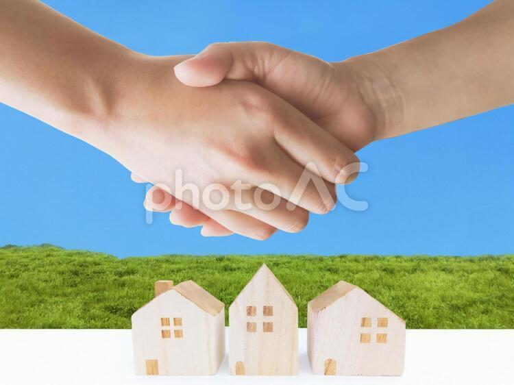 青空と草原と家の積木と男女の握手する手-新婚生活イメージの写真