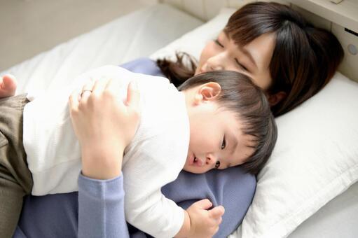 ベッドで昼寝をする親子