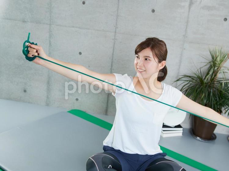 自宅でチューブトレーニングをする日本人女性の写真