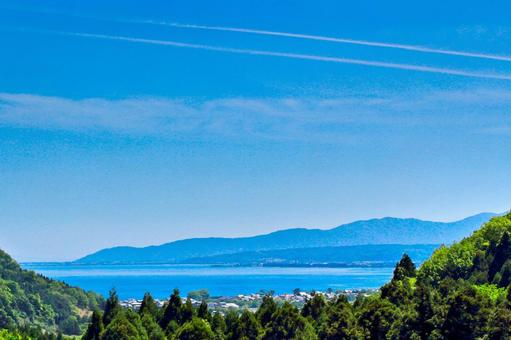 Distant view of Lake Biwa with blue sky and two contrails