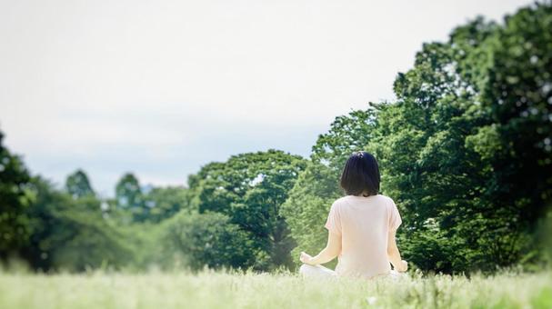 풍부한 자연 잔디에 명상을하는 여성