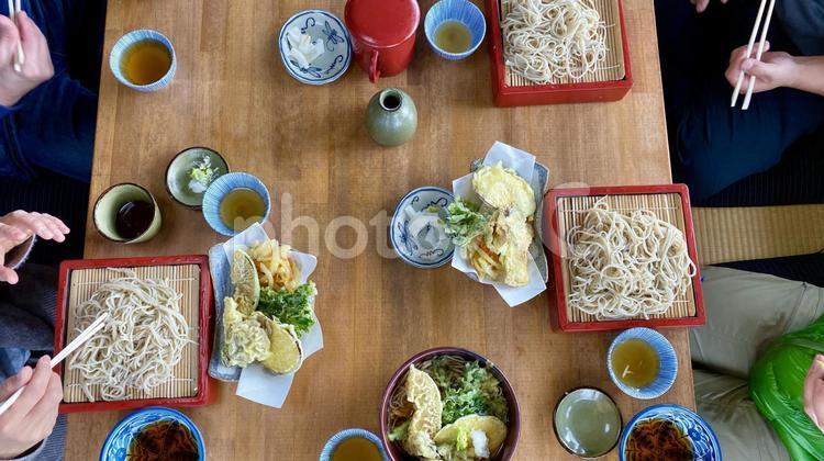 そばを食べる人たちの手 俯瞰の写真