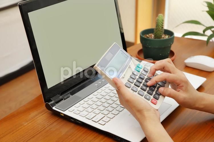 ノートパソコンと電卓で計算する女性と緑の観葉植物の写真