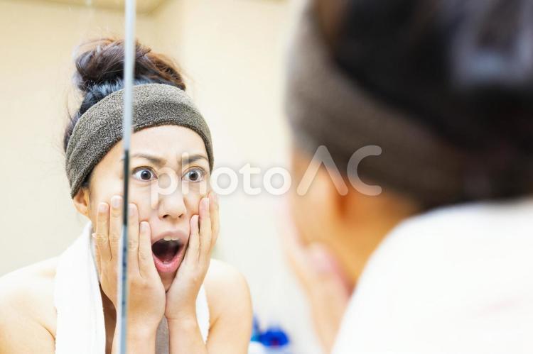 鏡を見てショックを受ける女性の写真