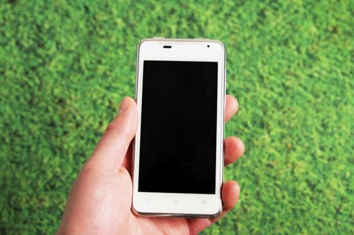 A state of trying to operate a white smartphone with both hands against the background of the lawn