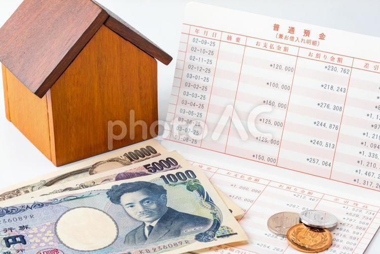 家計のやりくり・不動産・貯蓄イメージ(お金と預金通帳と戸建て住宅の模型)の写真