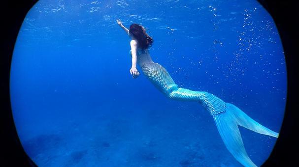 Mermaid aiming at the surface of the water Okinawa sea