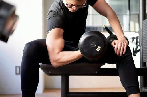 Asian man doing dumbbell curls in a training gym