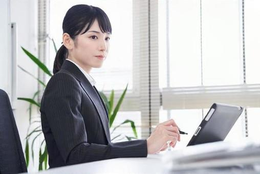 Japanese female business woman who converts paper materials into data using a tablet in the office