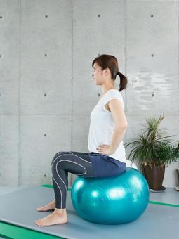 Japanese woman doing self-training with a balance ball