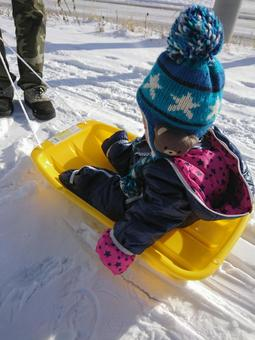 Baby riding a sled for the first time