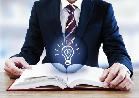 A businessman opening a thick book and a light bulb mark
