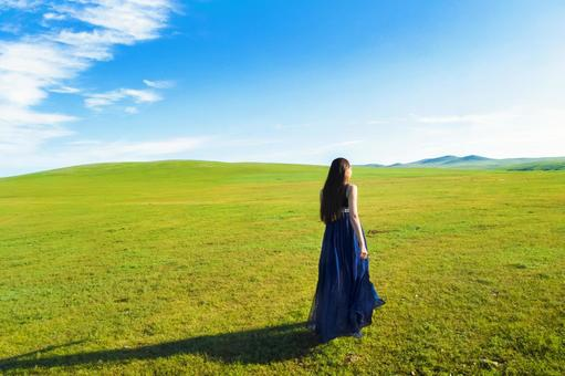 Woman in blue dress looking at Mongolian land