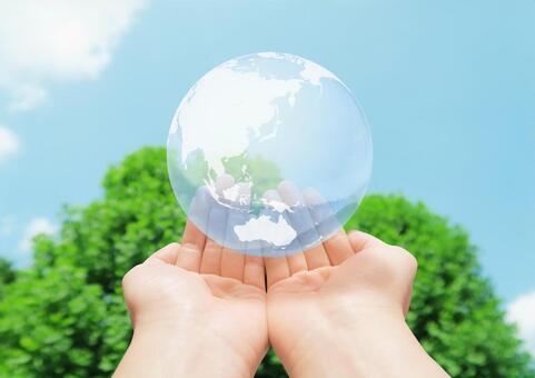 將全球環境放在您的手掌中-藍天和綠色背景