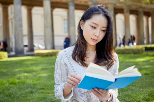 Asian woman reading a book on the lawn 1