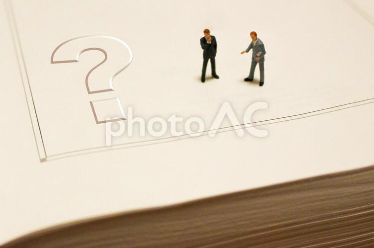 分厚い本とビジネスマン クエスチョンの写真