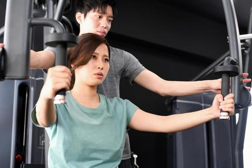 Asian women doing muscle training (chest press) on the machine and male trainers assisting