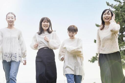 4 women walking while talking with a smile