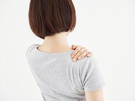 Woman holding a sore shoulder on a white background
