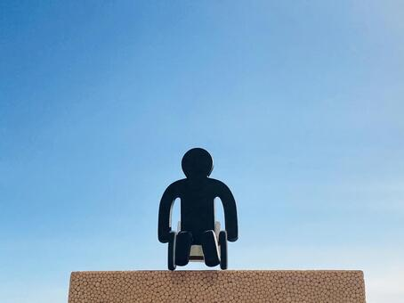 Black doll in a wheelchair and blue sky