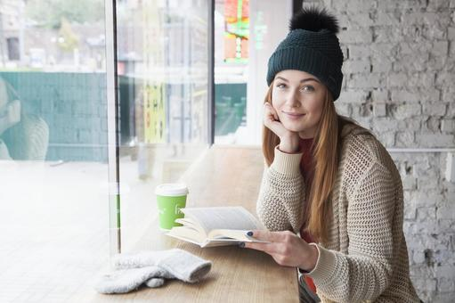 A woman reading a book at a cafe 2