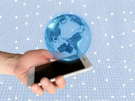 Smartphone in hand and the earth (image of the Internet)