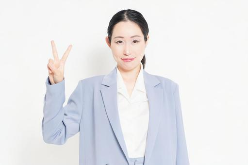 A woman standing in front of a white background and showing numbers by hand