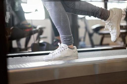 The feet of an Asian woman running on a treadmill