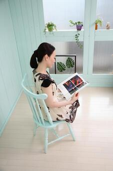 Sitting in a chair and reading a book Female 2