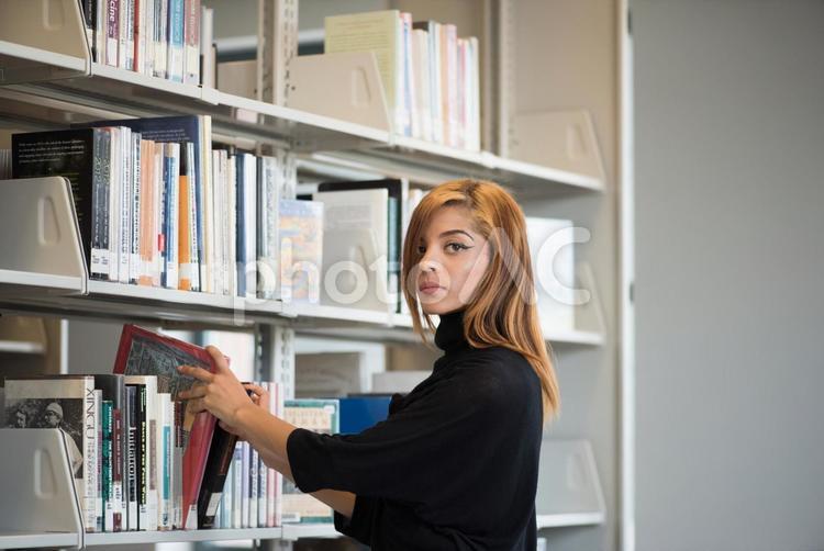 図書館 本を探す外国人女性1の写真