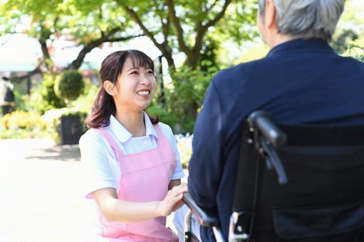 A care helper woman and a senior man in a wheelchair talking outdoors
