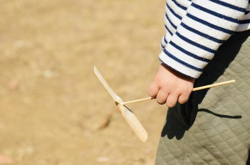 Hand of a young child holding a bamboo dragonfly