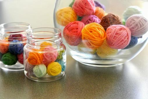 Miniature wool balls in bottles and glasses