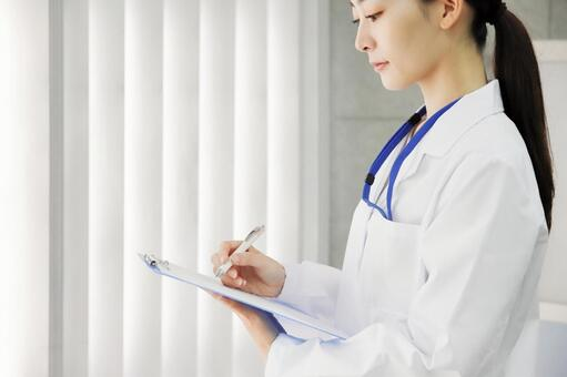 A woman in a white coat checks and records quality