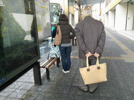 在公共汽车站等车的人